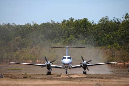 Small plane landing on bush airstrip