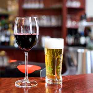 A glass of red wine and a glass of beer