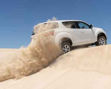 White car driving up a sand dune